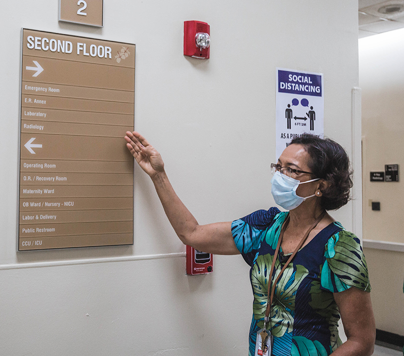 Maria Perez pointing to GMH second floor directory